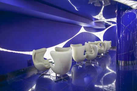 White rotating chairs and glass tables in a blue room with modern lighting. Interior in white and blue color scheme.