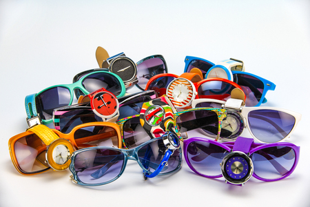 Collage of multi-colored wrist watches and sunglasses on a white background