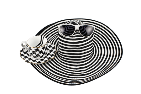 Summer wide-brimmed hat and cup with black and white pattern, on white background