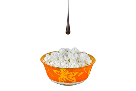 Orange bowl with cottage cheese and a drop of chocolate. White background.