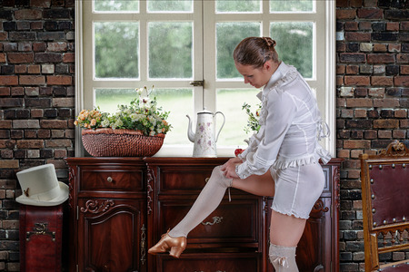 Chest of drawers of the Victorian era near the window. A dancer in a vintage suit adjusts her stockings before the performance.