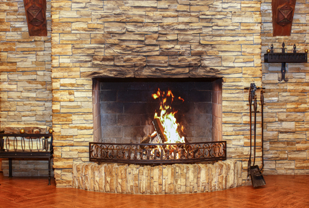 Burning fireplace close-up. Fireplace accessories in a large room with a stone wall