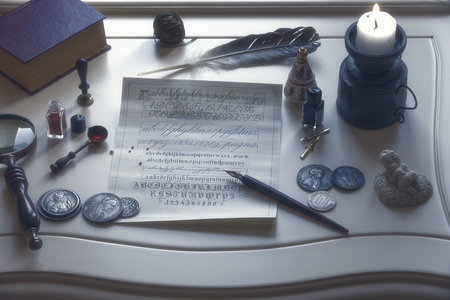 Candle, magnifier, old coins and writing materials on an antique table Archivio Fotografico