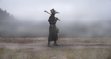 Époque médiévale. Le médecin de la peste marche le long de la route près du lac brumeux Banque d'images