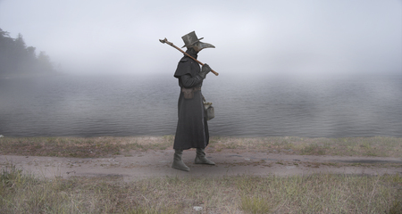 Medieval era. The plague doctor walks along the road near the misty lake Stock Photo