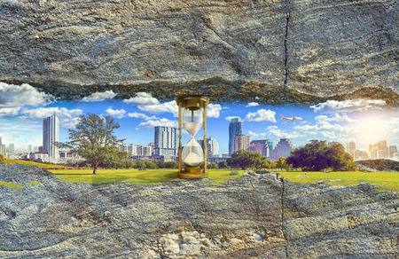 City in the horizontal space between the rocks. Hourglass supporting the rocky sky. People resting on the green lawn.