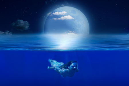 Sea, night, moon, starry sky. Girl swimming underwater