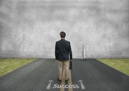 Un homme avec une mallette devant un mur de béton, symbolisant les difficultés Banque d'images
