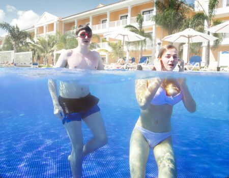 A young couple swims and dives in the pool of a tropical hotel