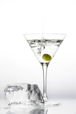 Martini glass, green olive berry and a large piece of melting ice