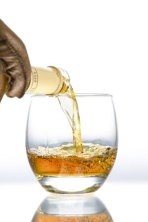 A hand in a leather glove pours alcohol into an oval glass