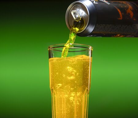 Carbonated energy drink pouring from an aluminum can into a glass
