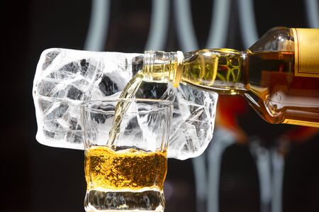 A stream of whiskey pours from a large bottle into a glass