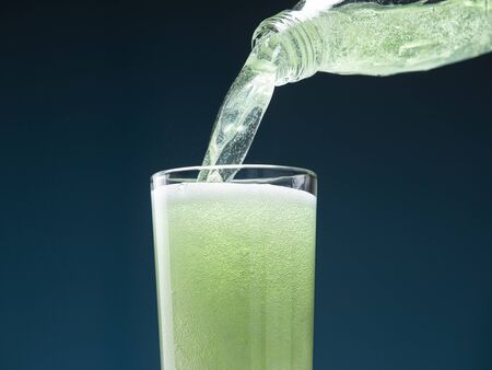 Mojito carbonated cocktail pours from a bottle into a glass