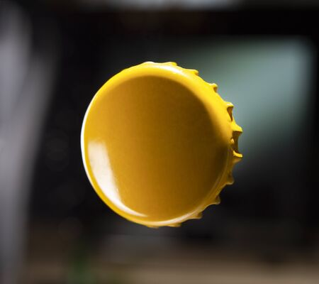 Yellow Metal Bottle Cap With Copy Space Isolated on dark Background.