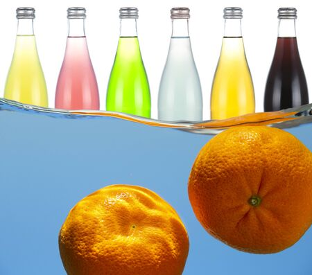 Bottles with various fruit sodas and tangerines in water