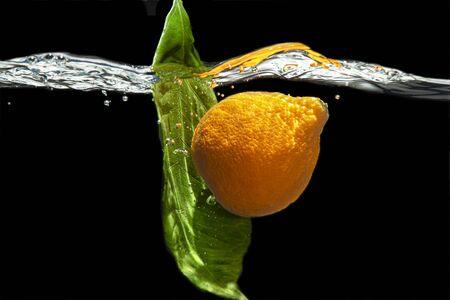 Mandarin and leaf of tangerine tree, submerged under water. Air bubbles.