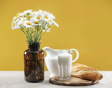 Daisies in a brown glass vase, porcelain jug, milk and bread
