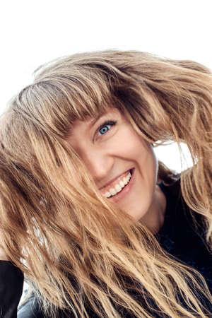 The face of a cheerful girl half hidden by hair