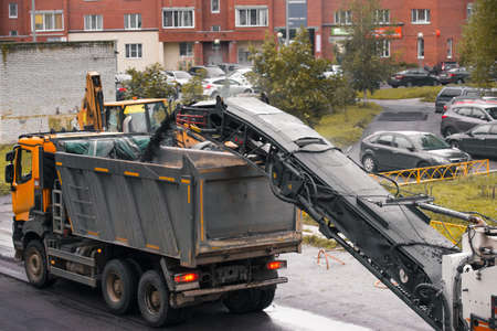 The removed asphalt is poured into the dump truck body from the conveyor of the cold milling machine Stok Fotoğraf