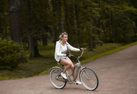 Woman rides a bicycle along the alleys of a summer park