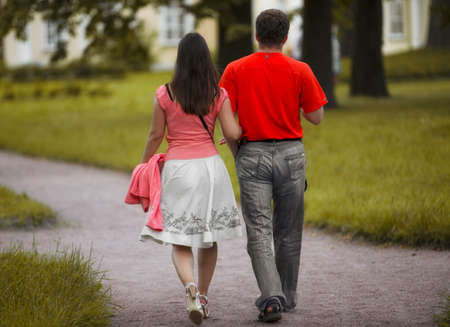 Young couple walking along the alley of the summer park Stok Fotoğraf