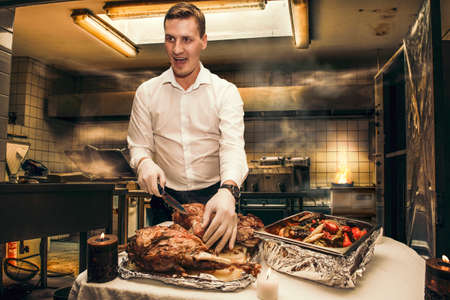 Young chef cuts fried lamb hams with a knife, in the smoky atmosphere of an old kitchen