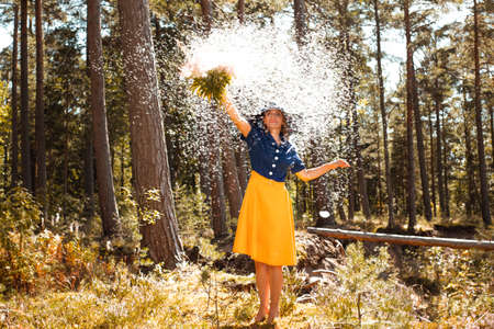 Young woman with a bouquet of wildflowers surrounded by fluffy parachutes of flower seeds Stok Fotoğraf