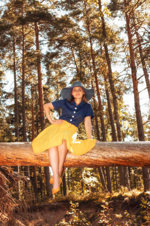 A girl in a yellow and blue dress and hat sits on a log over a cliff, her legs dangling