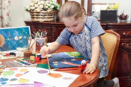 A child paints a papier mache astronaut figurine with a brush