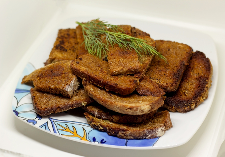 plate appetizing pieces of black bread with a sprig of dill fried with garlic Stok Fotoğraf - 98427244