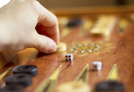 the hand of the player making his move in the backgammon party Stock Photo