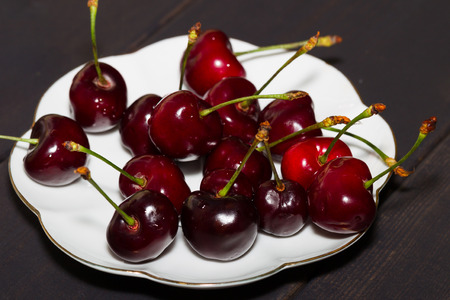 Berries of sweet cherry on a wooden table in a white bowl. Bright burgundy juicy berries. Dark background.