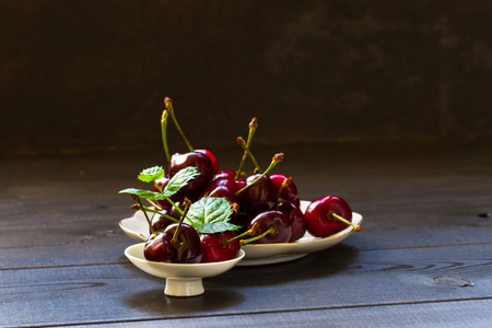 Cherry on a dark background with a sprig of mint. Food photography.