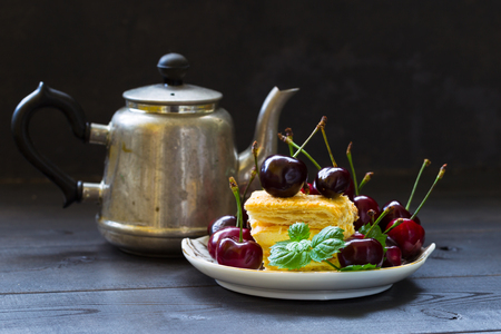 Still life with a teapot, a piece of puff cake, a sprig of mint and cherries. Dark background. Food photo. Фото со стока