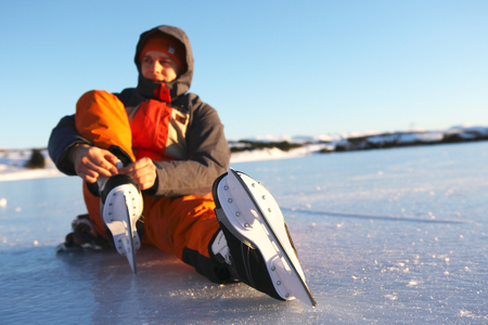 Young man sits on the ice tightening up the shoelaces on his ice skates Stock Photo