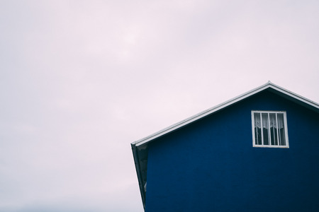 Blue house roof top with window grey sky background Stock Photo