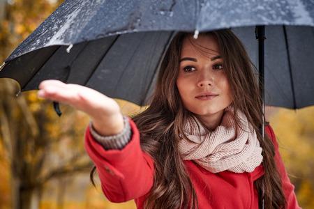 Een meisje in een rode jas met een zwarte paraplu in de regen in de herfst Stockfoto