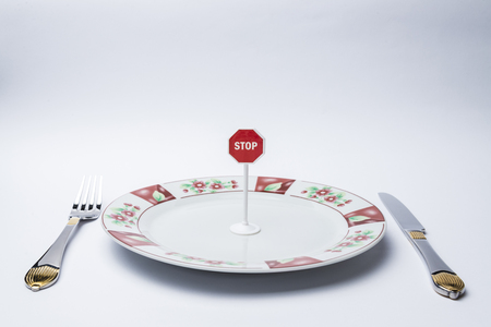 Fork, knife, plate on white background, and on the plate a stop sign