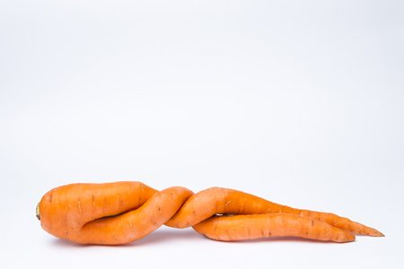 carrots of unusual shape lies on a white background.Copy space Stock Photo