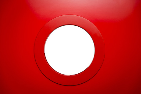 round white porthole in the red door Фото со стока