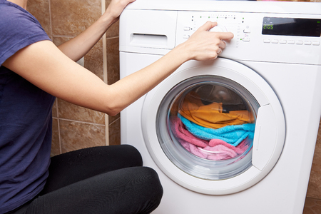The girl launches a washing machine with colored things