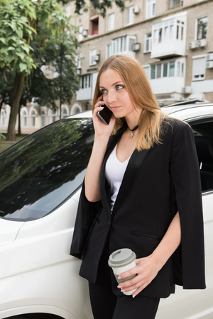 Beautiful girl with a cup talking on the phone near the car
