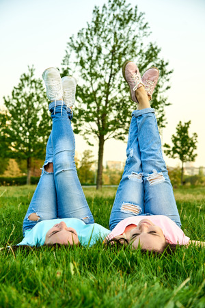 Two happy young girls lie on the grass with their legs up Foto de archivo