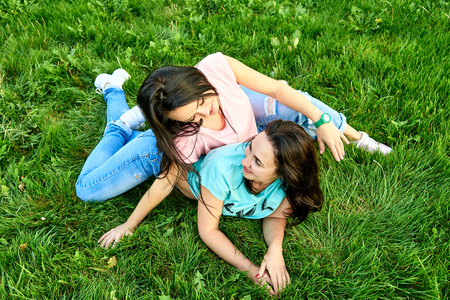 Two young happy girls lie on green grass