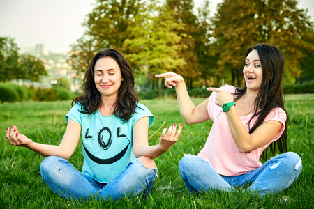A girl laughs at a friend who meditates in the park