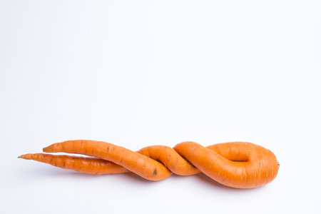 carrots of unusual shape lies on a white background