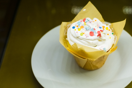 Cupcake with cream, glaze and decoration