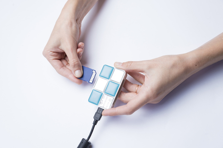 Hands of a girl inserting a memory card into a card reader on a white background Stock Photo