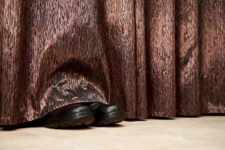 Boots stick out from under the curtains 스톡 콘텐츠